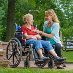 Healthcare professional listening through stethoscope to the heartbeat of a person in a wheelchair, both in an outdoor setting.