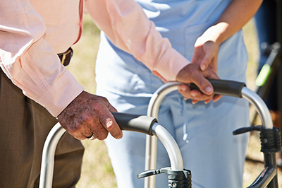 Midsection, healthcare worker helping senior man with walker