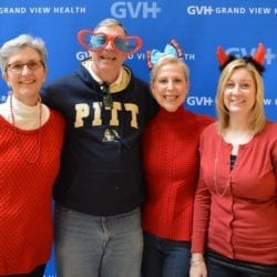 Four adults, one wearing oversized heart-shaped sunglasses, one wearing a bow headband, and one wearing devil horns - in front of blue GVH wall background at Heart Fair.