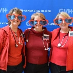 Three adults, all wearing oversized heart-shaped sunglasses - in front of blue GVH wall background at Heart Fair.