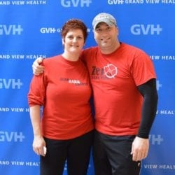 Two adults - in front of blue GVH wall background at Heart Fair.