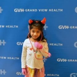 Child wearing devil horns - in front of blue GVH wall background at Heart Fair.