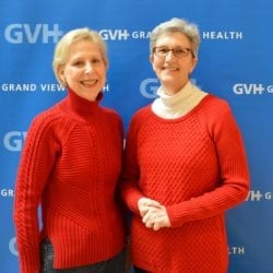 Two older women - in front of blue GVH wall background at Heart Fair.