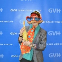 Person wearing oversized heart-shaped sunglasses, sailor hat, and a large orange polka-dotted tie while holding a rubber chicken - in front of blue GVH wall background at Heart Fair.