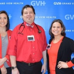 Three adults in medical attire - in front of blue GVH wall background at Heart Fair.