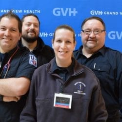 Four adults in medical attire - in front of blue GVH wall background at Heart Fair.