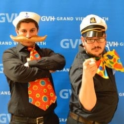 Two adults, one wearing a sailor hat and large mustache and large orange polka dot tie, one wearing a sailor hat and oversized polka dot bowtie - in front of blue GVH wall background at Heart Fair.