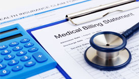 Close-up of a blue calculator and stethoscope sitting on top of a clipboard with a Medical Billing Statement.