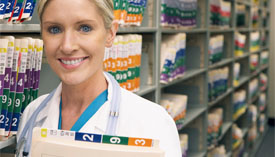 Medical professional smiling, standing in filing storage.