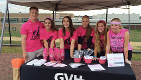 A team of six young women in pink shirts stands behind a GVH booth.