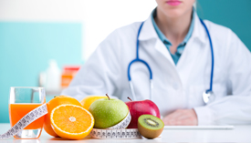 A measuring tape wraps around and between a small glass of juice, an orange half, a green and a red apple, and half a kiwi while a doctor in a white coat with a stethoscope around their neck sits in the background.