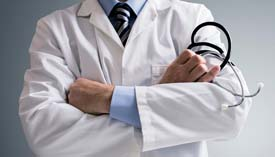 Close-up of doctor's torso, arms folded across chest and stethoscope in right hand.