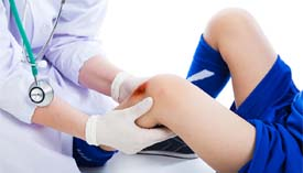 Doctor examines abrasion on young patient's knee.